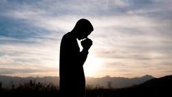 Silhouette eines Mannes im Gebet.