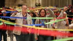 Als Zeichen ökumenischer Brücken verbinden die Teilnehmer des ökumenischen Gottesdienstes beim Katholikentag 2014 farbige Bänder miteinander.