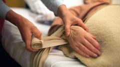 Eine Pflegerin fixiert die Haende einer verwirrten Altenheim-Bewohnerin an das Bett, um sie ruhig zu stellen.