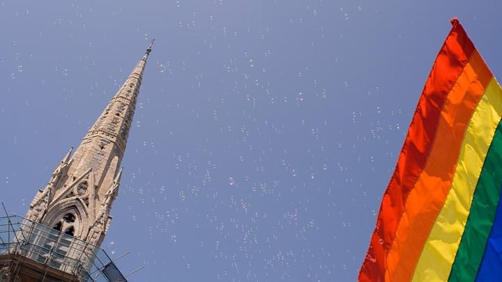 Regenbogenflagge und Kirchturm vor blauem Himmel.