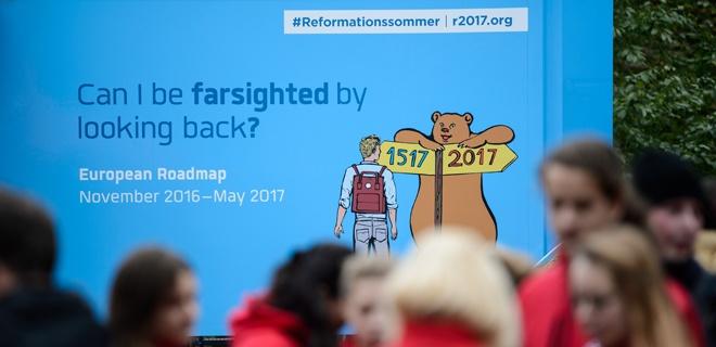 Seitenansicht des Reformations-Trucks mit Grafik, die einen jungen Mann mit Rucksack und einen Bären zeigt, der auf einem Doppelschild mit den Jahreszahlen 1517 und 2017 lehnt.