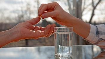 Eine jüngere Frau reicht einer älteren Frau eine Tablette.