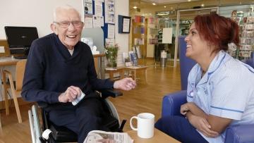 Eine Pflegerin scherzt mit einem Patienten.
