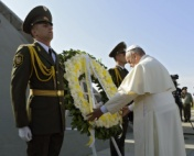 Papst vor Blumenkranz neben Soldaten