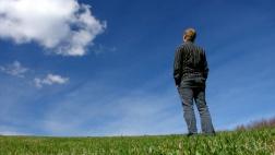 Ein Mann steht auf einer Wiese und blickt Richtung Himmel.
