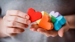 Bunte Herzen aus Papier liegen auf einer Hand.
