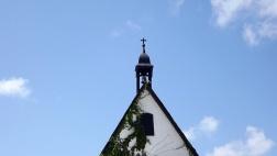 Kirchturmspitze mit Kreuz vor blauem Himmel.