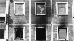 Rauchgeschwaerzte, eingeschlagene Fenster des Plattenbaus in Rostock-Lichtenhagen, der von rechtsradikalen Jugendlichen in der Nacht des 24.08.1992 angezuendet wurde