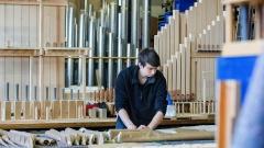 Ein Auszubildender zum Orgelbauer in der Orgelbaufirma Johannes Klais in Bonn verpackt eine neue Orgel der Christuskirche in Lima, Peru.