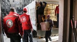Freiwillige des Roten Halbmondes entladen einen UN-Hilfskonvoi.