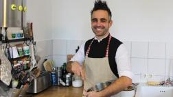 Pastor Steffen Paar steht mit umgebundener Küchenschürze in einer Küche und hält einen Topf in den Händen.