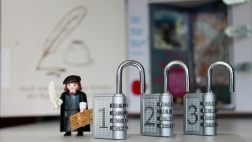 Eine kleine Martin luther Playmobilfigur steht neben drei geöffneten Schlössern, im Hintergrund steht die geöffnete Lutherbox