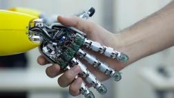 Roboter und Mensch schütteln sich die Hand.