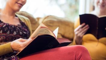 Zwei junge Frauen lesen in der Bibel.