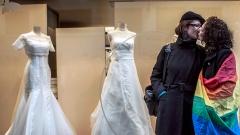 Zwei Frauen, eine mit Regenbogenflagge, küssen sich vor einem Geschäft für Brautmoden in Lyon, Frankreich.