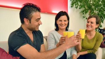 Henrike Alle, ihre Tochter Kristin und ihr Gast Abdullah Iqbal stoßen mit dem Joghurt-Getränk Mango Lassi an.