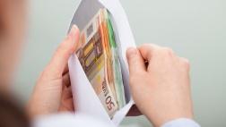 Nahaufnahme von Händen mit einem Briefumschlag voller Geldscheine.