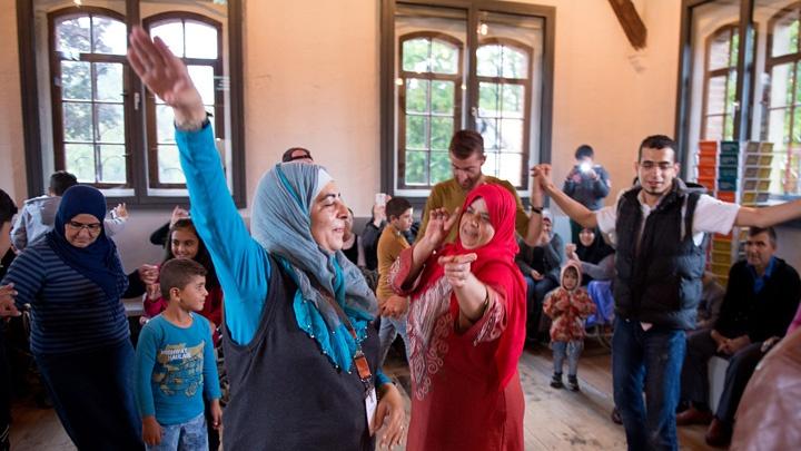 Flüchtlinge tanzen am 17.09.16 im Foyer des Museums Friedland bei Göttingen zu moderner syrischer Popmusik, die aus dem Handy kommt.