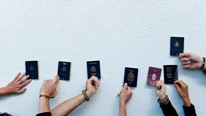 Backpacker aus verschiedenen Ländern halten ihre Reisepässe hoch.