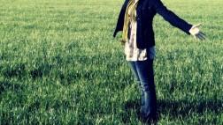 Eine Frau steht auf einer grünen Wiese und breitet die Arme aus.
