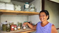 Eine Teilnehmerin des Partnerprojekts mit dem Kubanischen Kirchenrat steht neben einem Regal mit Einmachgläsern.