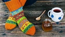 Warme Socken mit einer heißen Tasse Tee und Honig