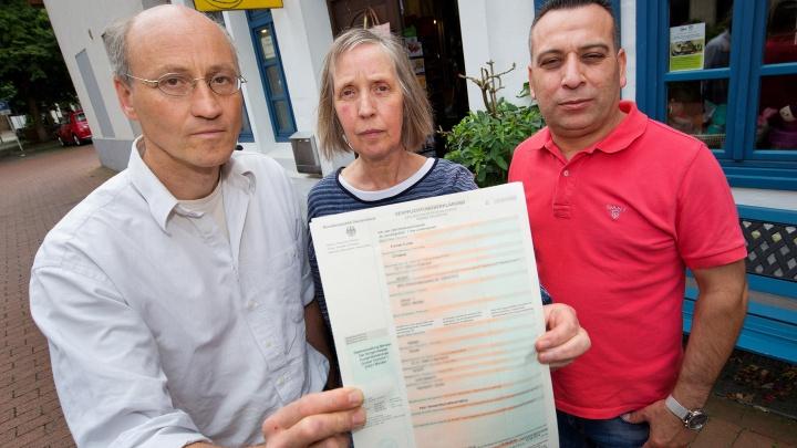 Die Eheleute Emmer-Funke und der Syrer Kameran Ebrahim, Schwiegersohn des geflüchteten Ehepaars, halten die Verpflichtungserklaerung in die Kamera.
