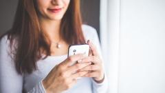 Frau hält ein Smartphone in den Händen.