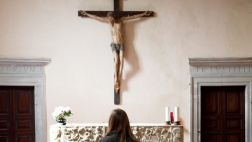 Eine Frau steht vor einem Altar in einer Kirche.
