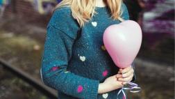 Junge Frau hält einen herzförmigen Luftballon in den Händen.