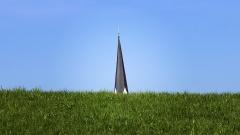 Ein Kirchturm ragt hinter einer grünen Wiese hervor.