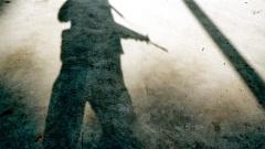 Schatten eines Mannes mit Gewehr