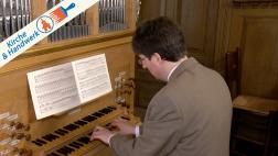 Ein Mann spielt eine Orgel.