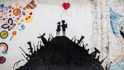 Ein Graffito an einer Wand einer Schule in Hasaka im Nordosten von Syrien zeigt in einem Erdhügel steckende Waffen. Auf der Kuppe stehen zwei Kinder mit einem roten Herz-Luftballon.