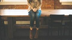 Eine Frau sitzt auf einem Tisch an dem zwei leere Stühle stehen.