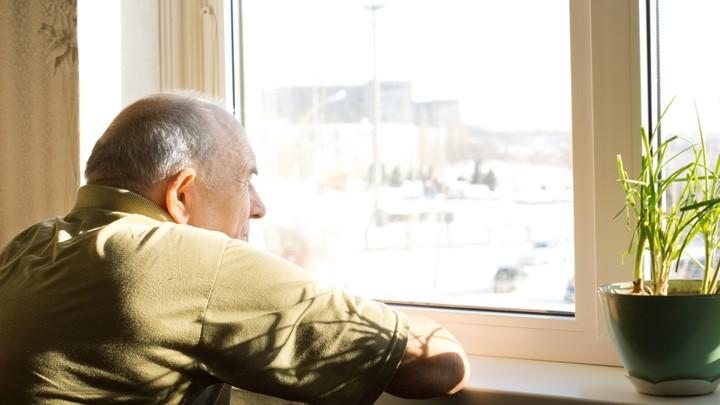 Ein älterer Mann blickt aus dem Fenster.