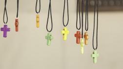 Kreuze in verschiedenen Farben an Lederbändern zum Umhängen.