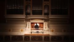 Organist spielt an einer Orgel.