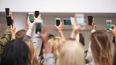 Jugendliche halten ihr Smartphone hoch.