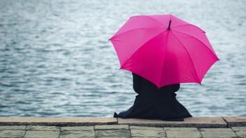 Eine in schwarz gekleidete Frau sitzt im Regen an einem Flussufer und hält einen pinken Regenschirm über sich.
