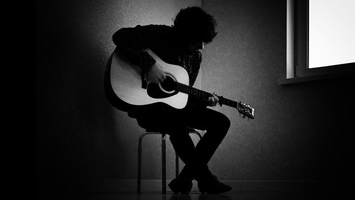 Mann spielt auf einer Gitarre.