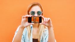 Eine Frau macht ein Selfie vor einer orangenen Wand.
