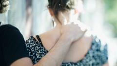 Ein Mann legt seinen Arm um eine Frau.