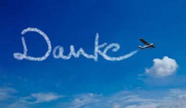Flugzeug schreibt das Wort Danke an den blauen Himmel
