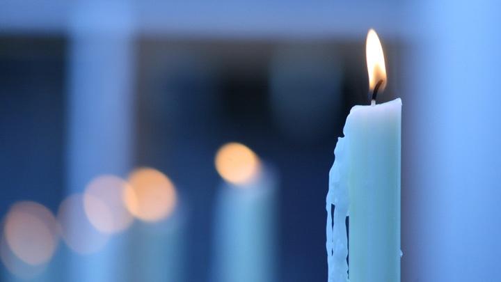 Kerze steht in einem Fenster.