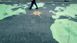 Ein Mann läuft über eine auf den Boden gemalte Weltkarte.