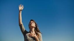 Frau streckt eine Hand zum Himmel und legt die andere auf ihr Herz.