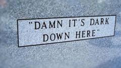 Grabsteininschrift 'Damn it's dark down here'