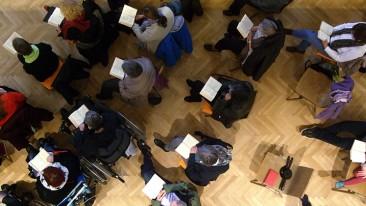 Menschen auf Stühlen, locker aufgereiht, von oben in einem Kirchenraum