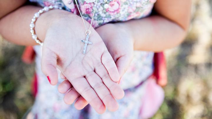 Junge Frau mit einem Kruzifix an einer Halskette.